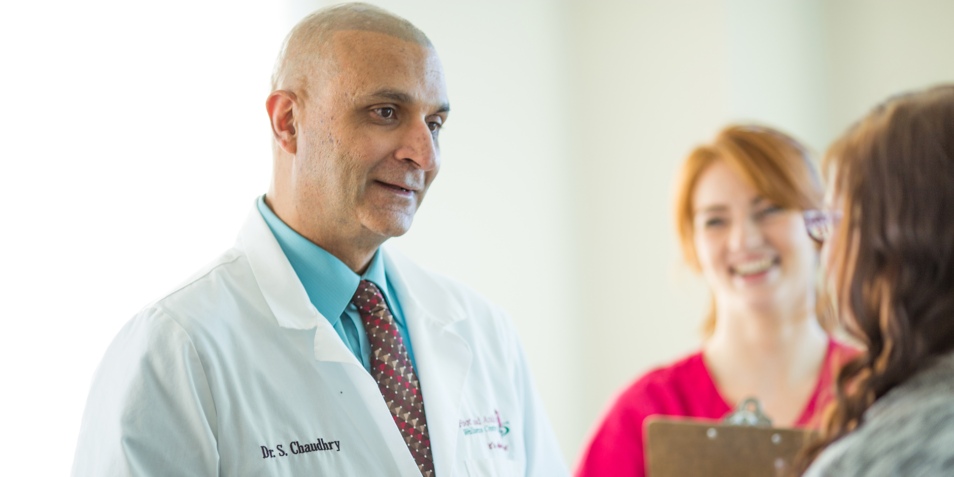Dr. Chaudhry and an employee greeting a female patient. The doctor is wearing a white coat, tie, and collared shirt.